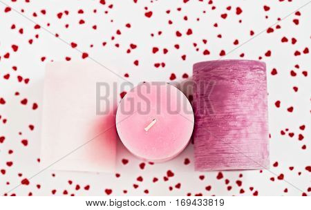 Three pink gradient candles on a white background with little red hearts flat lay. Valentine concept