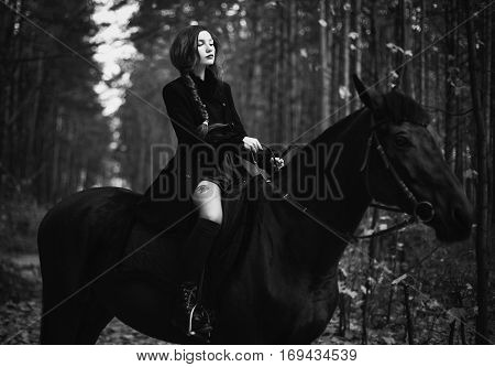 brave red-haired girl in a black coat and a red dress with long hair gathered in a braid a woman riding a horse in autumn forest beautiful strong stallion horse rider