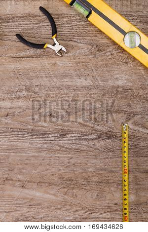 Building level, nippers and tape measure. Construction design. Wood rustic background.