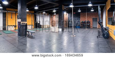 Contemporary spacious cross-fit gym with trainers sport equipment and a rope for climbing