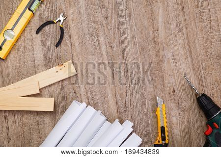 Building level, nippers and knife. Paper plans, drill and wooden planks. Wood rustic background.