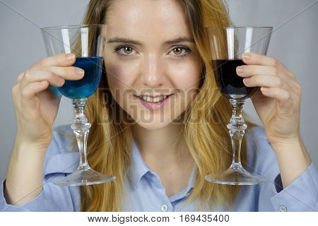Portrait of a pretty blond caucasian girl with light brown eyes holding with her hands two glasses of wine. One wine is dark red and one blue - choice, tastes, wines, flavors, health concept