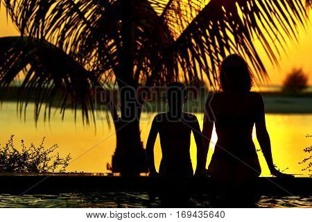 Silhouettes of mother and kid on tropical beach at sunset