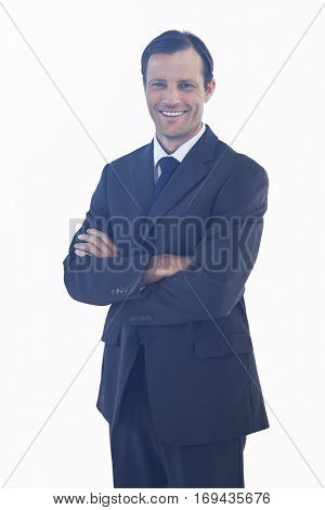 Charismatic smiling businessman standing with arms crossed on white background