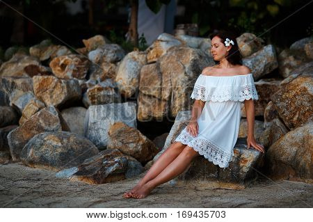 Young woman relaxing outdoors on the background of stone wall