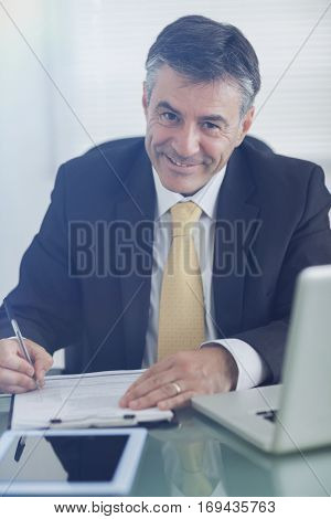 Business man smiling while working in his office