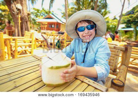 Cute little boy drinking coconut cocktail on tropical beach resort