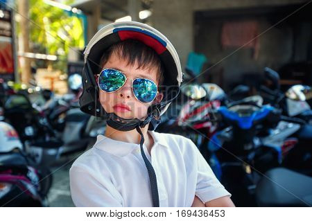 Portrait of cute little boy in helmet and sunglasses before riding a motorcycle with his parents
