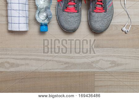 Fitness gym equipment. Sneakers, water bottle with towel. White headphones for music and sport. Workout footwear. Trainers with pink shoelace.