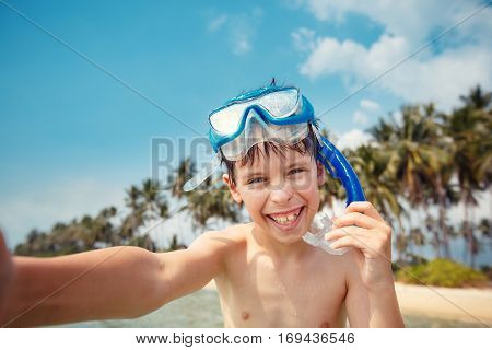 Cute little boy in snorkeling mask making selfie at tropical beach on exotic island during summer vacation
