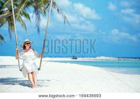 Beautiful woman swinging on a Tropical beach on Koh Phangan island. Thailand, Asia
