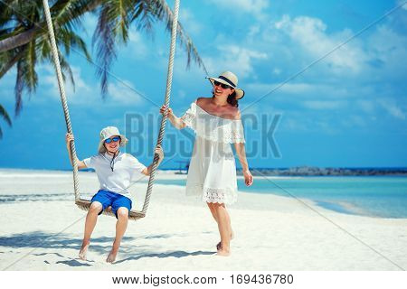 Young beautiful woman swinging her son on a tropical beach, Koh Phangan island. Thailand, Asia