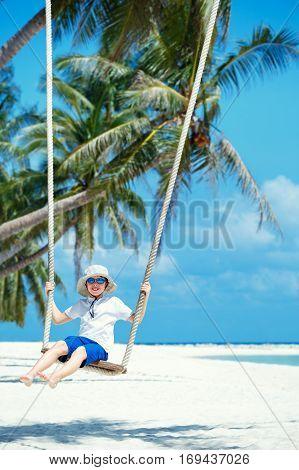 Cute boy having fun swinging at tropical island beach, Koh Phangan island. Thailand, Asia