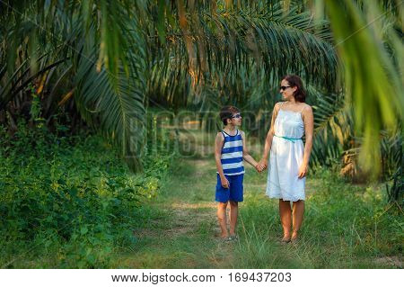 Young woman in white dress and her son walking in tropical forest during summer vacation