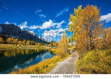 Canmore, near Banff Park. Path around the lake. The concept of hiking. Majestic mountains and autumn aspens reflected in the water