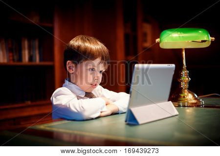 Cute little boy with a tablet pc indoors. Education, technology and children concept