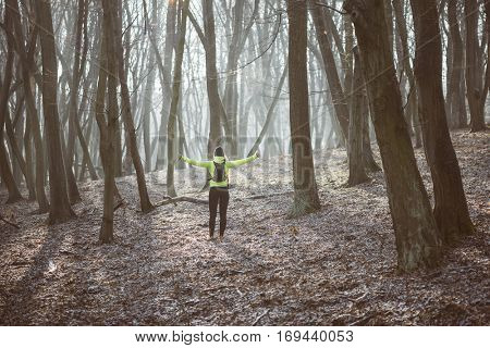 Young runner woman resting in forest after workout, arms outstretched.