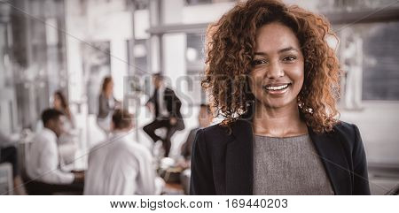 Portrait of smiling businesswoman holding disposable coffee cup in office