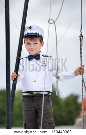 Cute toddler boy in captain costume enjoying boat ride at lake