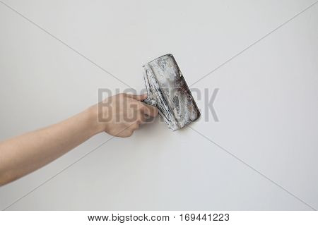 Working tool spatula in hand on a light background work plasterer painter to make repairs . Trowel in man's hand on a background of a white wall . Space for text