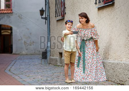 Young mother and her son making self portrait with a mobile phone in city street, Riga, Latvia