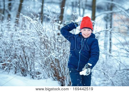 Cute little boy having fun with snowball fight winter outdoor