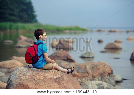 Little boy enjoying scenic view of rocks at the coast of Kasmu, north of Estonia