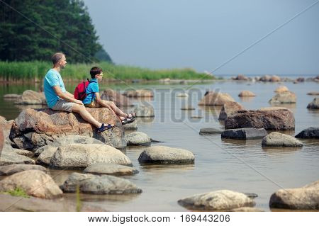 Family of two enjoying scenic view of rocks at the coast of Kasmu, north of Estonia