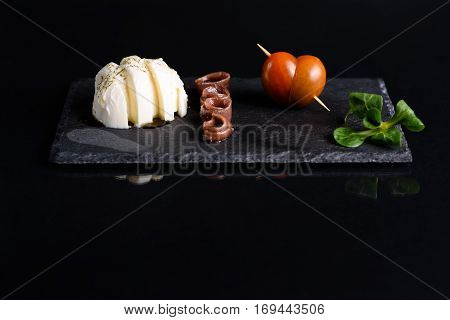 fresh anchovies, placed on a wooden table and accompanied by oil, tomatoes and parsley