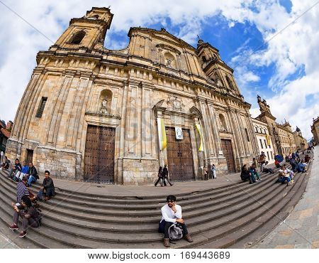 BOGOTA COLOMBIA - APRIL 23: Unidentified people relax in front of the primary cathedtral in Bolivar Square on April 23 2016 in Bogota Colombia.