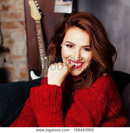 young pretty stylish woman in red winter sweater at couch in home interior happy smiling, lifestyle people concept close up