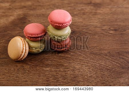 Macaroon cakes. Different types of macaron. Colorful almond cookies. French sweet dessert. Wooden rustic board.