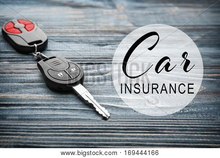 Car insurance concept. Car key with trinket on wooden background