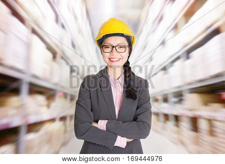 Young Asian female store manager with hard hat arms crossed standing in storehouse. Shelves with goods at background.