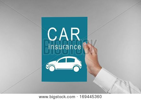 Car insurance concept. Male hand with paper on gray background