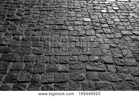 Black cobbled stone road background with reflection of light seen on the road. Black or dark grey stone pavement texture. Ancient paving stone background