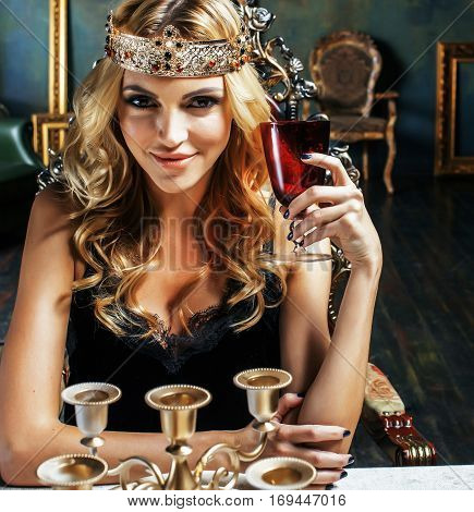 young blond woman wearing crown in fairy luxury interior with empty antique frames total wealth, rich lifestyle concept close up