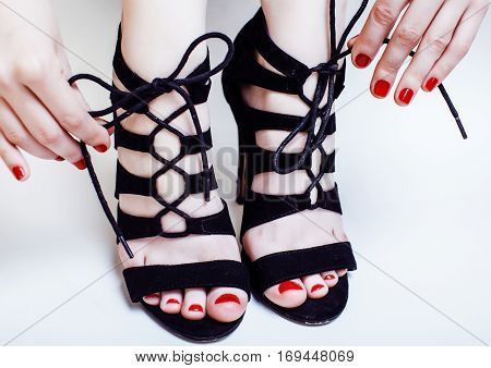 fashion concept people: woman with red nails manicure pedicure tying shoelaces on hight heel shoes isolated on white background close up stylish
