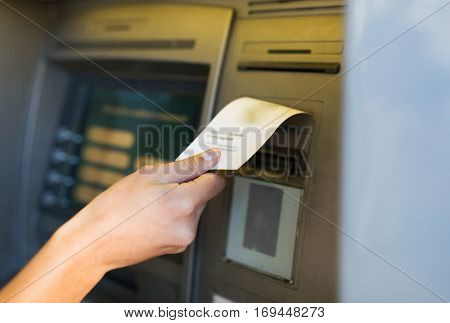 finance, money, bank and people concept - close up of hand taking receipt from atm machine