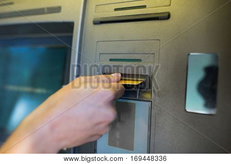 finance, money, bank and people concept - close up of hand inserting card to atm machine