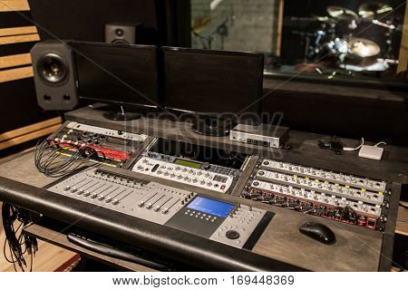 music, technology, electronics and equipment concept - mixing console and computer monitors at sound recording studio