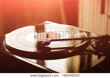 Vintage record player with vinyl disc, close-up. ray from the sunset.