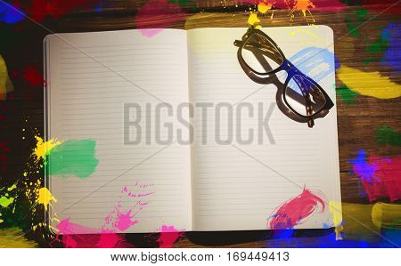 Frame of art supply against eyeglasses on book at desk with copy space