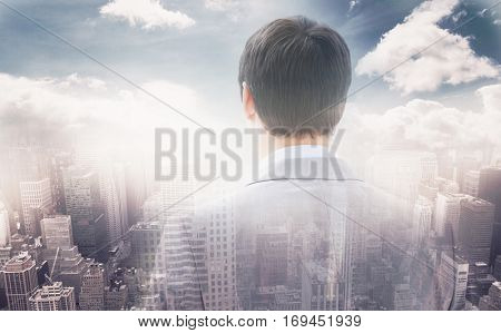 Rear view of businessman looking through window of building against aerial view of a city on a cloudy day 3d