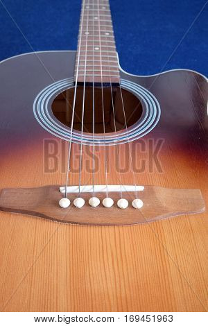 Classic acoustic six strings guitar sunburst color top from spruce with cutaway fragment isolated on black background vertical view closeup