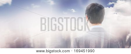 Rear view of businessman looking through window of building against aerial view of a city on a cloudy day with copy space 3d