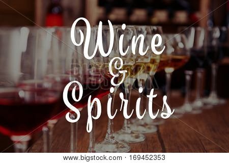 Text WINE AND SPIRITS on background. Glasses of different wine in row on table