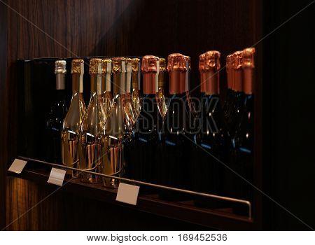 Wine bottles on wooden shelf at liquor store