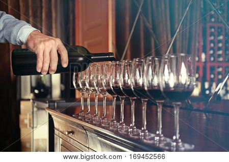 Man pouring red wine into glasses