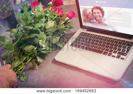 Dating website against laptop by flower on table